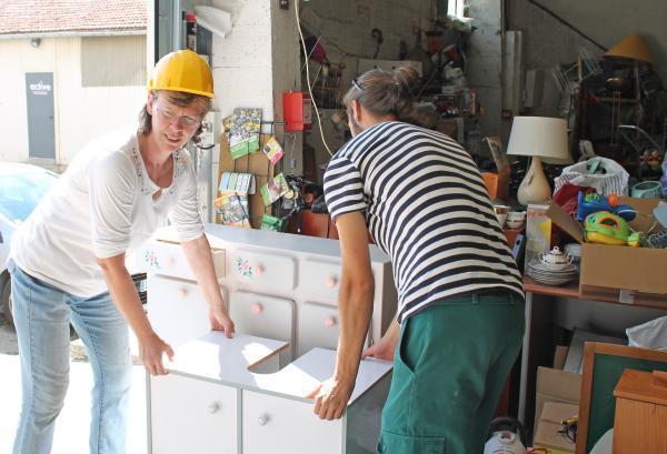 Tout l'après-midi, des habitants apportent des meubles et des objets usagés. Sophie et Paul font de la place dans l'espace de collecte, vite saturé.