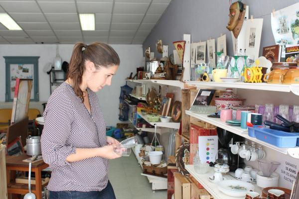 À la boutique, Fabienne est en pleine réflexion : comment agencer au mieux l'étagère pour mettre en valeur ces verres à vin ?