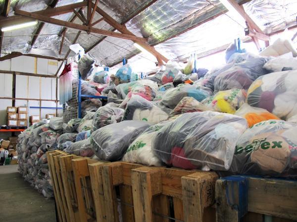 Dans un entrepôt, les sacs remplis d'habits attendent de passer par l'espace tri.