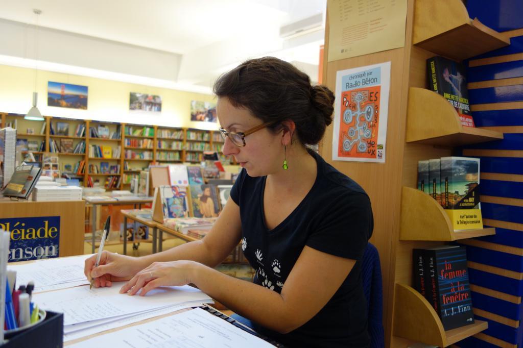 Claire, responsable du rayon polar, accroche des notes sur ses livres « coups de coeur ».